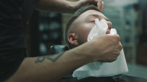Barber wipes off with a napkin the face of the client Live Action