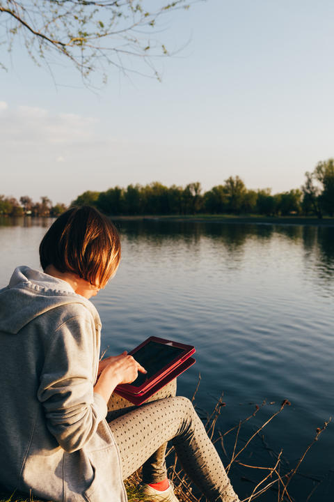 girl working with tablet at the river Photo