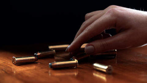A female hand takes a bullet 9 mm Footage