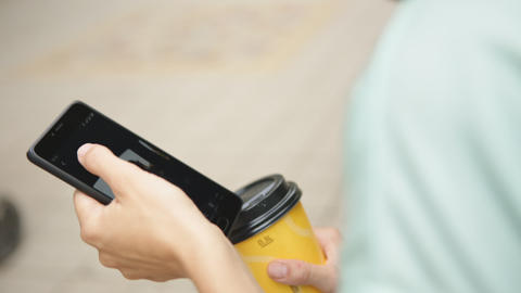 Woman drinking coffee and looking at phone Footage