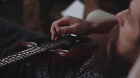 Hipster playing electric guitar, sprawled Stock Video Footage