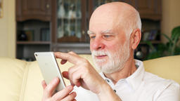 Senior man at home using cellphone, browsing, reading news. Active modern life Footage