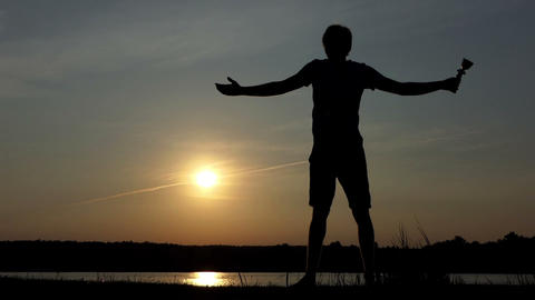 Happy man stands and raises a winner bowl at a lake in slo-mo Live Action