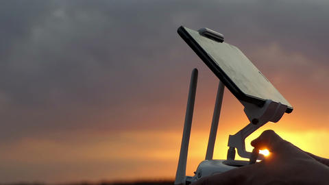 Woman's hands hold a control panel to operate a drone at sunset GIF