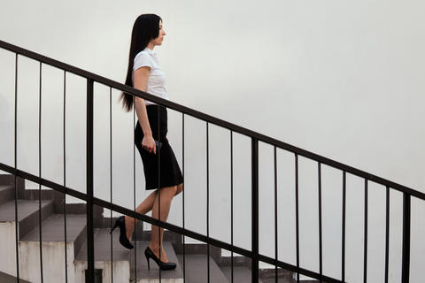Business woman goes down the stairs Photo