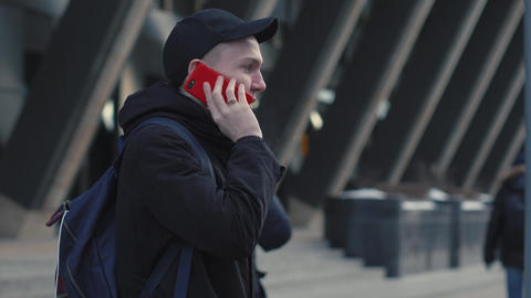 Young man calling by smart phone on urban street in modern city Live Action