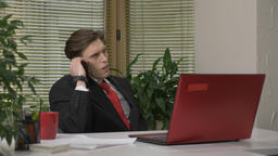 Young man in a suit sitting in the office, speaking on the phone, smartphone Footage