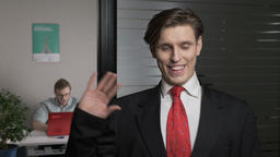 Young successful businessman in suit waving his hand, gesture of greeting Footage