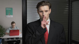 Young successful businessman in suit showing a sign of silence. Man works on a Footage