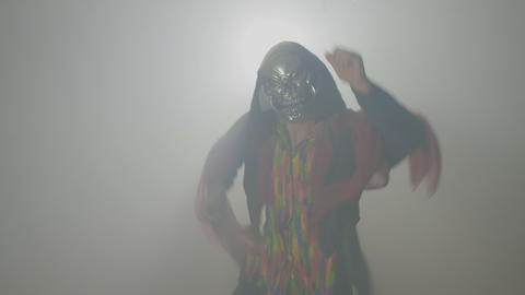 Malefic evil creature wearing a mask and doing the funny zombie dance in fog on Footage