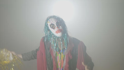Evil clown coming out from smoke taking his mask off and doing the killing Footage