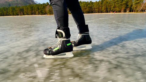 Long male legs in black leggins with hockey skates. Outdoor ice skating on the Footage