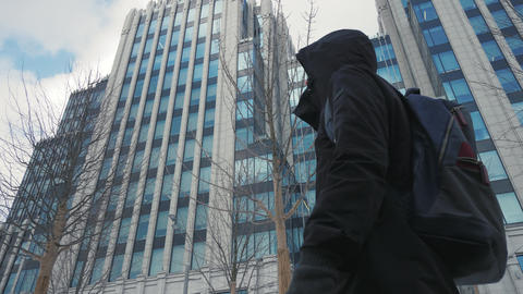 Man in black jacket with hood on head and backpack walking city street Footage