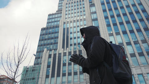 Man in black jacket and backpack rubbing hands and walking on city street Footage
