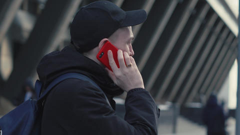 Man in black cap and jacket talking by smart phone on background cityscape Footage