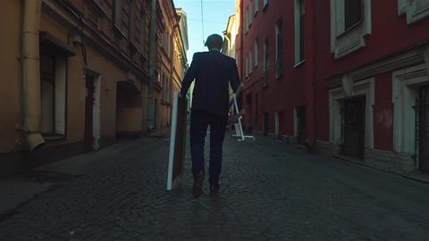 Artist Walking On The Street Between The Houses Footage