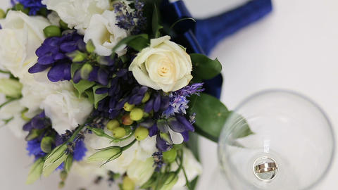 Beautiful Bridal Bouquet And Wedding Rings In A Glass Of Wine stock footage