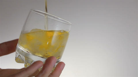 Whisky is poured over ice in GLASS on man hand Footage