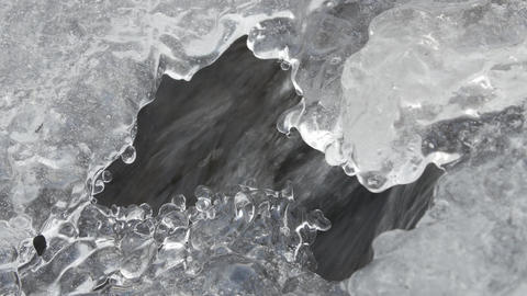 Frozen Mountain Stream. Under the ice build up running mountain stream close-up Live Action