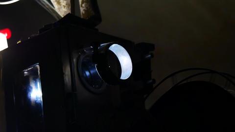 Vintage Retro Film cinema Projector Man is adjusting the film roll During Footage