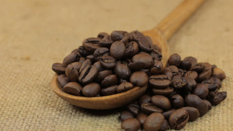 Rotating a spoon, overflowing with coffee beans, lying on burlap Footage