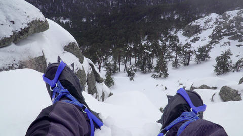 Feet with cranpons resting among rocks on top of snowy mountain Footage
