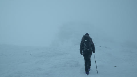 Hiker goes into the fog on the snowy mountain Footage