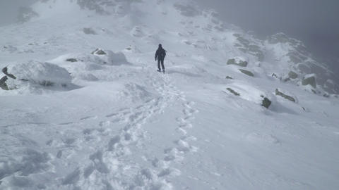 Tracking shot in the footsteps of an explorer ascending to the summit of the Footage