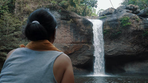 Woman admires the beautiful waterfall Footage