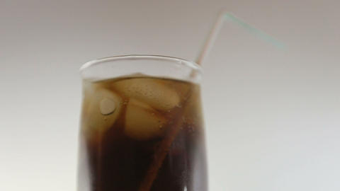 cola with ice in a glass with a straw Live Action