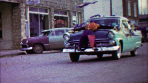 1959: Mannequin strapped to decorated parade car hood Footage