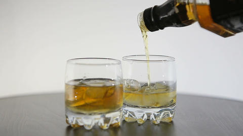 Whisky is poured over ice in two GLASS on wooden table Footage