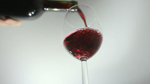 Pouring red wine from the bottle into a glass Footage