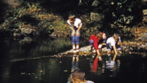 1959: Kids play water reflection looking for aquatic wildlife Footage