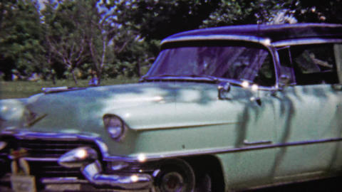 1959: Teal Cadillac 4 door classic car parked in outdoor green space Live Action