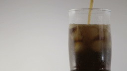 Cola with ice. Pouring Cola with Ice and bubbles in glass Footage