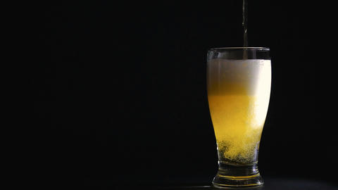 Beer in glass with bubbles on black background ビデオ