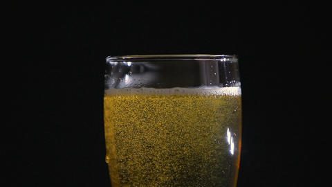 Beer in glass with bubbles on black background.Closeup Footage