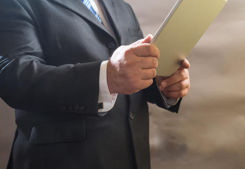 Close - up of adult businessman standing in suit and use tablet Photo