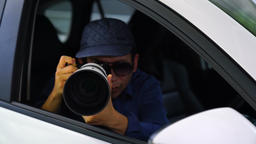 4K Spy, paparazzi or detective in the car, shooting on camera. Shot on RED EPIC GIF