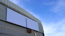 Man erects billboard poster for advertising. Blank wall for copy space GIF