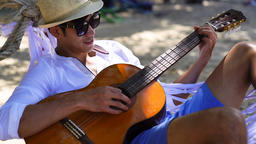 Happy playing guitar at the beach Archivo