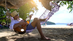 Happy playing guitar at the beach Live Action