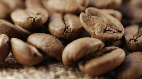Close up of coffee beans. In front of the camera rotates plate with coffee beans Live Action