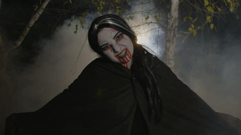 Malefic female zombie vampire getting out from a foggy forest at night in the Footage