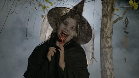 Evil witch zombie with blood on her mouth putting a halloween spell on victim Footage