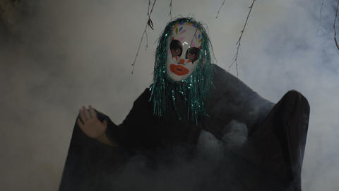 Crazy evil halloween clown coming up from a foggy wood and doing a ritual dance Footage