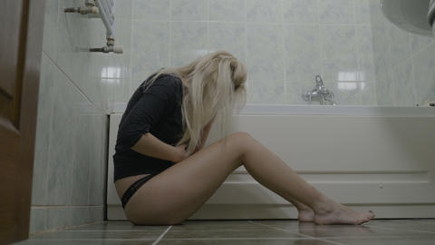 Sad sexy attractive young blonde woman sitting on bathroom floor and crying Footage