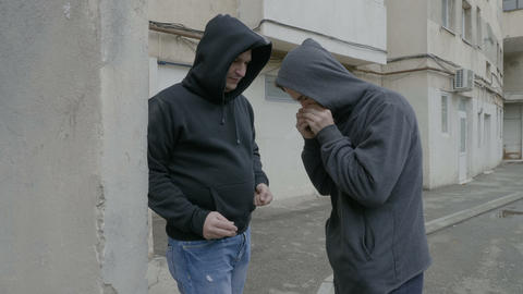 Narcotic dangerous men in hoods exchanging drugs for cash money in a poor Live Action