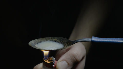 Close up of a man drug consumer heating heroin using a spoon and lighter and Footage